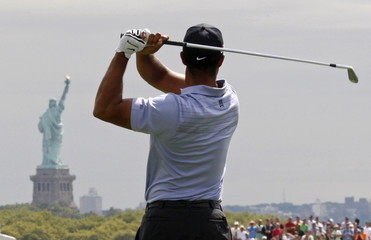 New York's Statue of Liberty is seen in the background as Tiger Woods of the U.S. hits off the second tee during first round play at The Barclays golf tournament