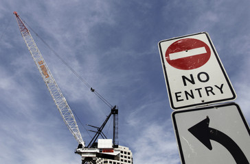 A road sign is seen in front of a crane at a residential construction site in Sydney