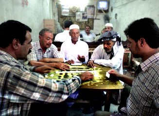 IRAQI MEN PLAY DOMINOS IN CAFE IN BAGHDAD.
