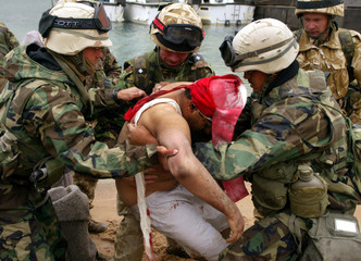 COALITION FORCE MEMBERS CARRY INJURED IRAQI IN THE PORT OF UMM-QASR.