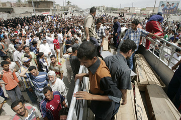 Residents attend the funeral for victims of a market bomb attack in Baghdad