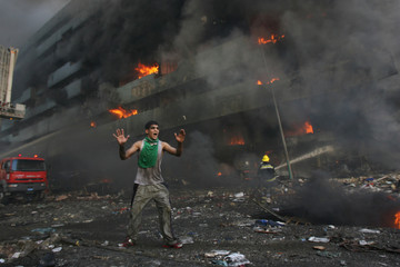 BEST QUALITY AVAILABLE A man runs down a street warning people to flee shortly after a twin car bomb attack at Shorja market in Baghdad