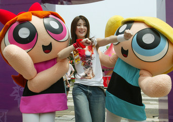 HONG KONG POP STAR KELLY CHAN POSES NEXT TO THE CARTOON CHARACTERS INHONG KONG.
