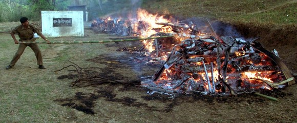 AN INDIAN BORDER SECURITY FORCE TROOPER LIGHTS THE PYRES DURING A CREMATION CEREMONY IN TURA.