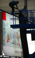 WORKERS DRAW A CURTAIN OVER POSTER WITH THE NEW LOGO OF GERMAN MOBILCOMAG AT CEBIT COMPUTER FAIR ...