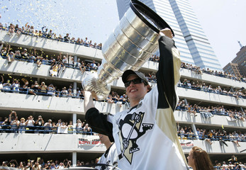 Pittsburgh Penguins captain Sidney Crosby hoists the Stanley Cup over his head during the Stanley Cup victory parade in Pittsburgh