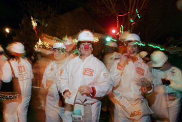 Revelers dressed as engineers walk through the Marigny neighborhood during the Krewe du Vieux parade in New Orleans