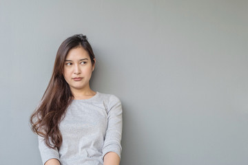 Closeup asian woman sitting and look at space with thinking face on blurred cement wall textured background with copy space