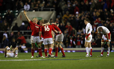 Wales players celebrate defeating England  in Six Nations rugby union match at Twickenham in London