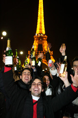 Revellers celebrate the New Year at the foot of the Eiffel tower in Paris January 1, 2006...