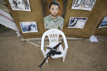 An assault rifle and a knife are seen next to pictures of a fallen soldier during a war exhibition in Tehran