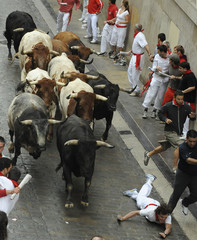 Runners are chased by a pack of Miura fighting bulls on Santo Domingo street on the seventh day of the running of the bulls at the San Fermin festival