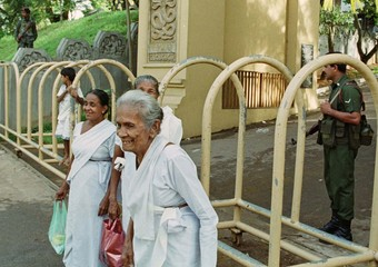 SRILANKAN BUDDHIST WOMEN FILE PAST SOLDIERS AS THEY LEAVE A TEMPLE.