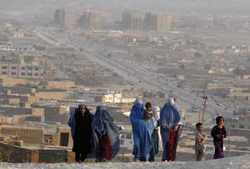 Goup of Afghan women and their children walk up a hill overlooking part of Kabul