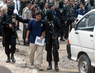 Indonesian police officers escort Rois, an Australian embassy bombing suspect, during a ...