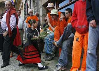 "A girl dressed as a ""pinorra"" hits men with a pine branch during the Pinochada festival in northern Spain"