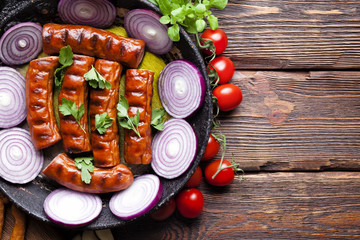 Cooked sausage with onion in a pan and fresh vegetables on wooden table