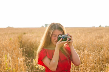 Young woman in the field with vintage camera.