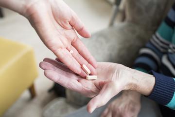 woman hands pills to an older woman