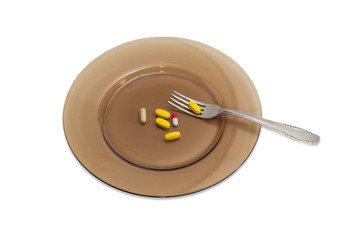 Different dietary supplements on the dark glass dish with fork