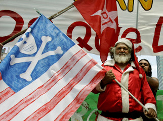 A Chilean dressed as Santa Claus carries a U.S. flag painted with a skull and crossbones in protest ..