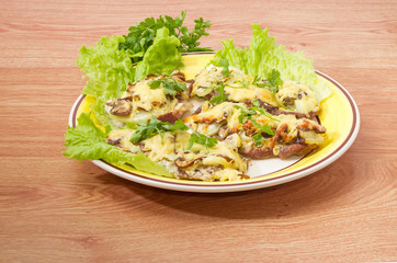 Pork chops baked with onion, mushrooms and cheese on dish