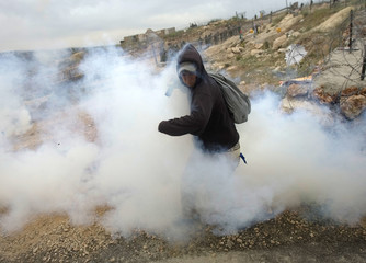 A protester reacts as a tear gas canister fired by Israeli soldiers lands near him in Bilin