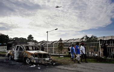 Solomon Islanders walk past a burned out police car outside a destroyed casino in Honiara
