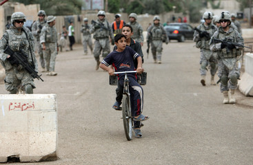 Boys ride a bicycle in front of U.S soldiers as they patrol a village near Baquba in Diyala province