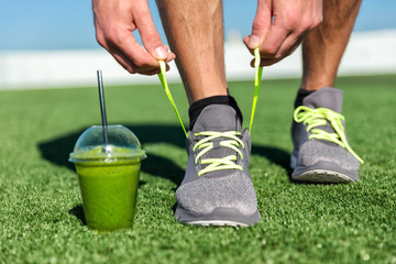 Green smoothie fitness man tying running shoes