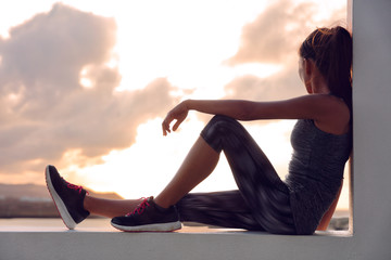 Fitness athlete runner woman relaxing in sunset Wall mural