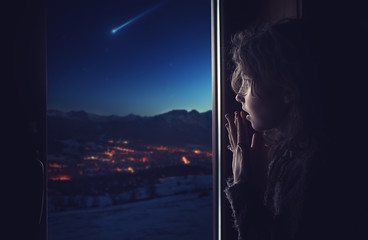 The girl looks out the window at the falling star