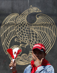 A supporter of former Thai Prime Minister Thaksin Shinawatra uses a noise maker as he smokes during a protest outside the Ministry of Finance in Bangkok