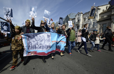 People of Chinese province Heilongjiang hold pictures of their relatives, who fought in 2nd Far Eastern front's 88th international detachment during World War Two, as they take part in Immortal Regiment march during Victory Day celebrations in Vladivostok