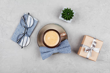 Morning coffee mug, gift, glasses and bowtie on stone table top view in flat lay style for breakfast on Happy Fathers Day.