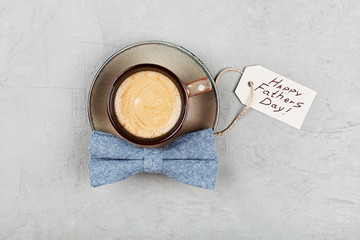 Morning cup of coffee and bowtie on stone table top view in flat lay style for breakfast on Happy Fathers Day.