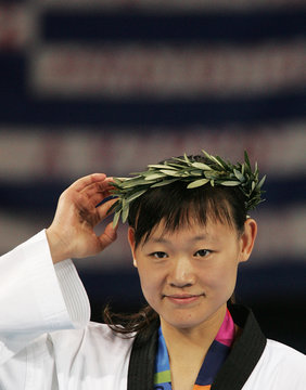 China's Luo Wei adjusts her laurel during the medal ceremony winning gold after the women's under 67 ...
