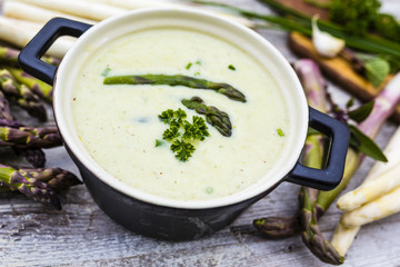 Delicious creamy asparagus soup on a wooden background.
