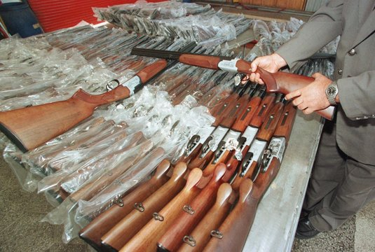 A custom officer checks one of the 115 seized hunting rifles at the Kapitan Andreevo border crossing..