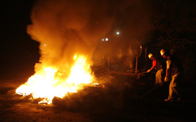 Labour union workers at Ssangyong Motor set fire to used tyres placed as barricades at the Ssangyong Motor plant in Pyeongtaek