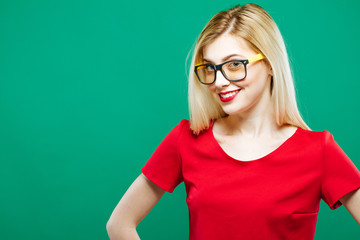 Portrait of Smiling Surprised Girl Wearing Red Top and Eyeglasses. Sensual Pretty Blonde with Long Hair is Posing on Green Background in Studio.