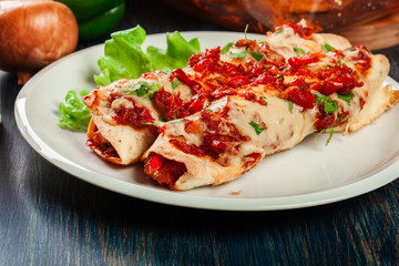 Traditional mexican enchiladas with chicken meat, spicy tomato sauce and cheese on a plate