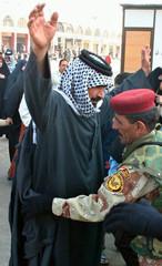 Iraqi policemen check residents outside Immam Ali shrine in Najaf
