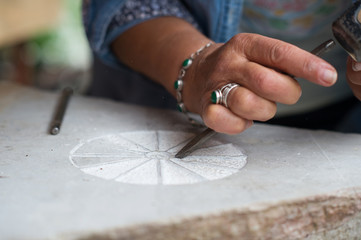 Close Up of Craftsman carving cosmogram in stone.