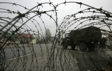 A KFOR vehicle passes by a barb wire near the main bridge in the ethnically divided Kosovo town of Mitrovica