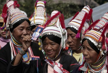 Akha hilltribe women hold campaign photos of a candidate during a rally in Mae Aye