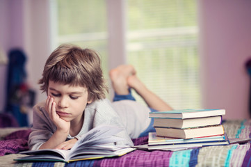 Cute little boy lying on bed reading next to stack of books
