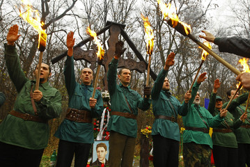 Men carry torches and salute during ceremony commemorating death of their leader Codreanu in Tancabesti forest