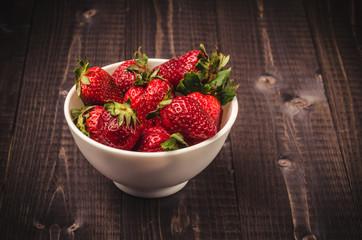 tasty strawberry on a dark wooden background/strawberry in a white bowl on a dark wooden background