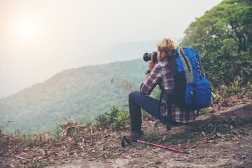 Rare of young traveller man with backpack standing in mountain and taking a photo. Male hiker photographing a beautiful mountain landscape.